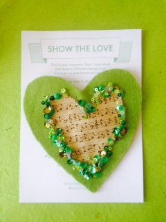 A handmade green heart with sequins and musical notes